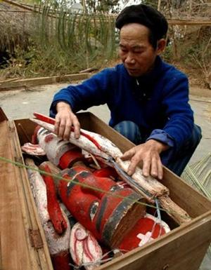 Ông Ma Quang Mai - tộc trưởng tộc rối Tày thôn Thẩm Rộc bên các con rối cổ.